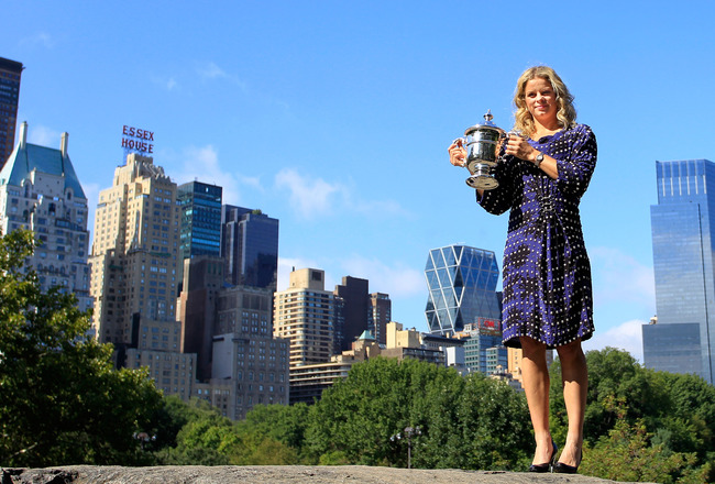 NEW YORK - SEPTEMBER 13:  Kim Clijsters of Belgium, 2010 U.S. Open Champion, wearing a dress designed by Dries Van Noten poses with the trophy while in Central Park on September 13, 2010 in New York City.  (Photo by Chris Trotman/Getty Images)