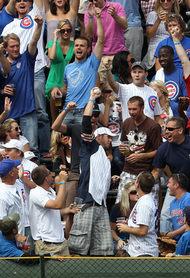 CHICAGO - SEPTEMBER 05: A fan in the left field bleachers holds up a home run ball hit by Aramis Ramirez of the Chicago Cubs against the New York Mets at Wrigley Field on September 5, 2010 in Chicago, Illinois. (Photo by Jonathan Daniel/Getty Images)