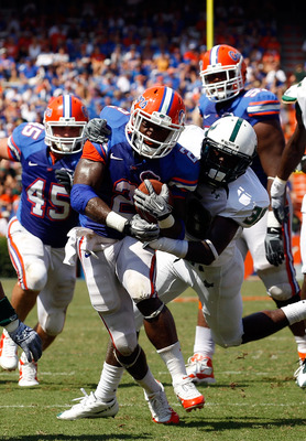 GAINESVILLE, FL - SEPTEMBER 11:  Jeffery Demps #2 of the Florida Gators breaks the tackle of Ricardo Dixon #38 of the South Florida Bulls during a game at Ben Hill Griffin Stadium on September 11, 2010 in Gainesville, Florida.  (Photo by Sam Greenwood/Get
