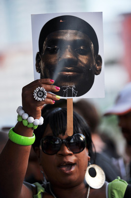 MIAMI - JULY 09:  A ticketed guest holds up the face of LeBron James before Chris Bosh #1, Dwyane Wade #3 and LeBron James #6 of the Miami Heat are presented to fans during a welcome party at American Airlines Arena on July 9, 2010 in Miami, Florida.  (Ph