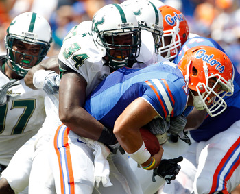 GAINESVILLE, FL - SEPTEMBER 11:  Quarterback Trey Burton #13 of the Florida Gators is tackled by Devekeyan Lattimore #34 of the South Florida Bulls  during a game at Ben Hill Griffin Stadium on September 11, 2010 in Gainesville, Florida.  (Photo by Sam Gr