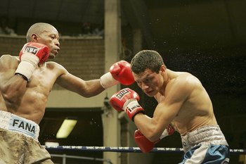 JOHANNESBURG, SOUTH AFRICA - DECEMBER 08: Mzonke Fana and Roberto Arrieta in action during the IBF junior lightweight eliminator between Mzonke Fana and Roberto Arrieta at Nasrec Indoor Arena on December 8, 2006 in Johannesburg, South Africa. (Photo by Le