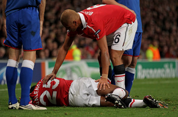 MANCHESTER, ENGLAND - SEPTEMBER 14:  Wes Brown of Manchester United comforts his injured team mate Antonio Valencia during the UEFA Champions League Group C match between Manchester United and Rangers at Old Trafford on September 14, 2010 in Manchester, E