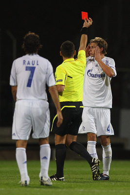 LYON, FRANCE - SEPTEMBER 14:  Benedikt Hoewedes (R) of Schalke is shown a red card by referee Ivan Bebek after a foul on Jimmy Briand during the UEFA Champions League Group B match between Olympique Lyonnais and FC Schalke 04 at the Stade de Gerland on Se