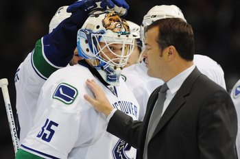 EDMONTON, AB - SEPTEMBER 22:  Head Coach Alain Vigneault of the Vancouver Canucks congratulates goaltender Cory Schneider #35 of the Vancouver Canucks after the shoot-out overtime against the Edmonton Oilers during an NHL preseason game on September 22, 2