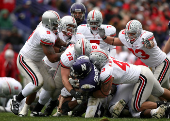 EVANSTON, IL - NOVEMBER 08:  Stephan Simmons #25 of the Northwestern Wildcats is tackled by Nate Williams #43 and Dexter Larimore #72 of the Ohio State Buckeyes at Ryan Stadium on November 8, 2008 in Evanston, Illinois  (Photo by Jonathan Ferrey/Getty Ima