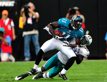 JACKSONVILLE, FL - DECEMBER 13:  Mike Sims-Walker #11 of the Jacksonville Jaguars is tackled by Gibril Wilson #28 of the Miami Dolphins during the game at Jacksonville Municipal Stadium on December 13, 2009 in Jacksonville, Florida.  The Dolpnins won 14-1