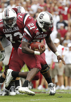 COLUMBIA, SC - SEPTEMBER 11: Tailback Marcus Lattimore #21 of the South Carolina Gamecocks runs with the ball while guard Rokevious Watkins #73 looks on during the game against the Georgia Bulldogs at Williams-Brice Stadium on September 11, 2010 in Columb