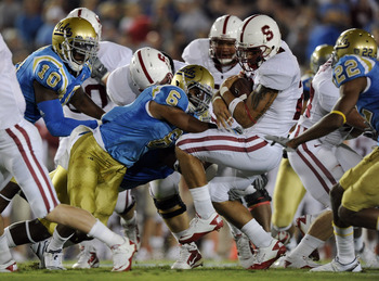 PASADENA, CA - SEPTEMBER 11:  Tyler Gaffney #25 of Stanford is hit by Tony Dye #6 of UCLA during the first quarter at the Rose Bowl on September 11, 2010 in Pasadena, California.  (Photo by Harry How/Getty Images)