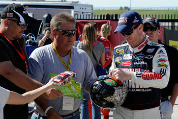 HAMPTON, GA - SEPTEMBER 04:  Dale Earnhardt Jr. (R), driver of the #88 AMP Energy/National Guard Chevrolet, signs his autograph for fans during practice for the NASCAR Sprint Cup Series Emory Healthcare 500 at Atlanta Motor Speedway on September 4, 2010 i