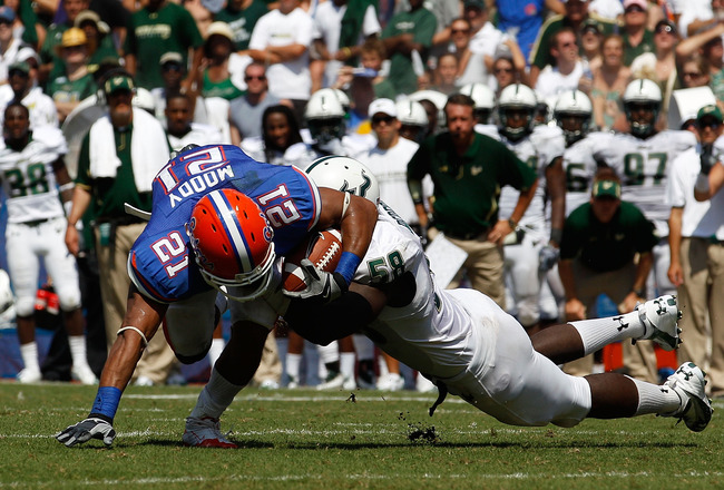 GAINESVILLE, FL - SEPTEMBER 11:  Emmanuel Moody #21 of the Florida Gators attempts to run past David Bedford #58 of the South Florida Bulls during a game at Ben Hill Griffin Stadium on September 11, 2010 in Gainesville, Florida.  (Photo by Sam Greenwood/G