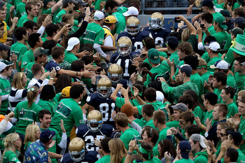 SOUTH BEND, IN - SEPTEMBER 04: Players from the Notre Dame Fighting Irish walk to the field through the student section for warm-ups before a game against the Purdue Boilermakers at Notre Dame Stadium on September 4, 2010 in South Bend, Indiana. Notre Dam