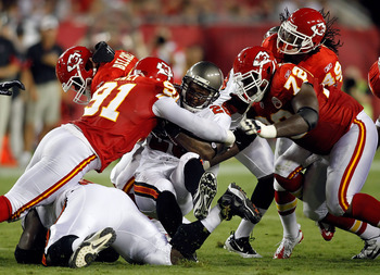 TAMPA, FL - AUGUST 21:  Defenders Tamba Hali #91 and Glenn Dorsey #72 of the Kansas City Chiefs tackle running back Derrick Ward #28 of the Tampa Bay Buccaneers during a preseason game at Raymond James Stadium on August 21, 2010 in Tampa, Florida.  (Photo