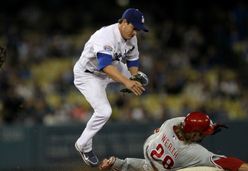 LOS ANGELES - AUGUST 30:  Second baseman Ryan Theriot #13 of the Los Angeles Dodgers lands hard as he jumps overJayson Werth #28 of the Philadelphia Phillies on an attempted double play on August 30, 2010 at Dodger Stadium  in Los Angeles, California.  (P