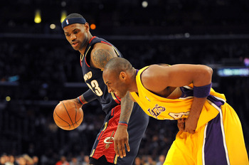 LOS ANGELES, CA - JANUARY 19:  LeBron James #23 of the Cleveland Cavaliers drives the ball against  Kobe Bryant #24 of the Los Angeles Lakers as Kobe  hunches over after he injures his hand during the first quarter at Staples Center on January 19, 2009 in