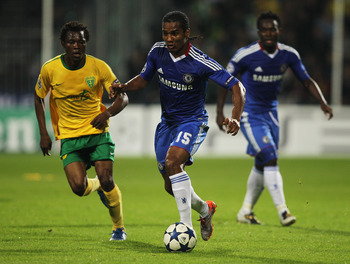 ZILINA, SLOVAKIA - SEPTEMBER 15:  Florent Malouda of Chelsea is chased by Babatounde Bello of MSK Zilina during the UEFA Champions League Group F match between MSK Zilina and Chelsea at the Pod Dubnom Stadium on September 15, 2010 in Zilina, Slovakia.  (P