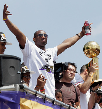 LOS ANGELES, CA - JUNE 21:  Los Angeles Lakers guard Kobe Bryant (L) waves to the crowd while riding in the victory parade for the the NBA basketball champion team on June 21, 2010 in Los Angeles, California. The Lakers beat the Boston Celtics 87-79 in 7