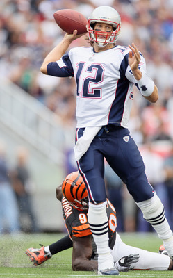 FOXBORO, MA - SEPTEMBER 12:  Tom Brady #12 of the New England Patriots scrambles as Antwan Odom #98 of the Cincinnati Bengals is unable to make the sack during the NFL season opener on September 12, 2010 at Gillette Stadium in Foxboro, Massachusetts.  (Ph