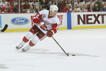 DETROIT, MI - JUNE 13:  Center Igor Larionov #8 of the Detroit Red Wings skates with the puck against the Carolina Hurricanes during game five of the NHL Stanley Cup Finals on June 13, 2002 at the Joe Louis Arena in Detroit, Michigan.  The Red Wings won 3