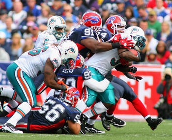 ORCHARD PARK, NY - SEPTEMBER 12: Ricky Williams #34 of the Miami Dolphins is tackled by the Buffalo Bills  defense during the NFL season opener at Ralph Wilson Stadium on September 12, 2010 in Orchard Park, New York. Miami won 15-10. (Photo by Rick Stewar