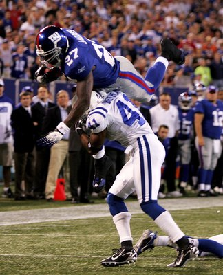 EAST RUTHERFORD, NJ - SEPTEMBER 10:  Brandon Jacobs #29 of the New York Giants dives over Antoine Bethea #41 of the Indianapolis Colts on September 10, 2006 at Giants Stadium in East Rutherford, New Jersey.  (Photo by Travis Lindquist/Getty Images)