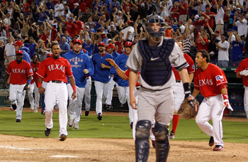 ARLINGTON, TX - SEPTEMBER 10:  The Texas Rangers celebrate at home plate after Nelson Cruz #17 hit the game-winning home run in the bottom of the 13th inning against the New York Yankees on September 10, 2010 at Rangers Ballpark in Arlington, Texas.  (Pho