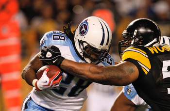 PITTSBURGH, PA - SEPTEMBER 10: Running back Chris Johnson #28 of the Tennessee Titans runs with the football as he is grabbed by LaMarr Woodley #56 of the Pittsburgh Steelers at Heinz Field on September 10, 2009 in Pittsburgh, Pennsylvania. The Steelers d