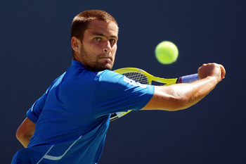 NEW YORK - SEPTEMBER 11:  Mikhail Youzhny of Russia returns a shot while playing against Rafael Nadal of Spain during his men's singles semifinal match on day thirteen of the 2010 U.S. Open at the USTA Billie Jean King National Tennis Center on September