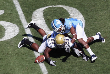CHAPEL HILL, NC - SEPTEMBER 18:  Roddy Jones #20 of the Georgia Tech Yellow Jackets dives for a loose ball with Tre Boston #10 of the North Carolina Tar Heels during their game at Kenan Stadium on September 18, 2010 in Chapel Hill, North Carolina.  (Photo