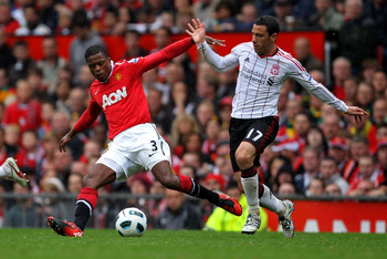MANCHESTER, ENGLAND - SEPTEMBER 19:  Patrice Evra of Manchester United tussles for posession with Maxi Rodriguez of Liverpool during the Barclays Premier League match between Manchester United and Liverpool at Old Trafford on September 19, 2010 in Manches