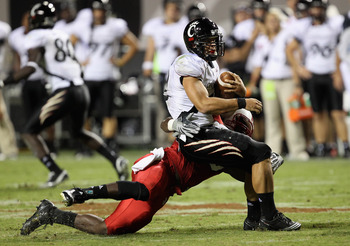 RALEIGH, NC - SEPTEMBER 16:  Zack Collaros #12 of the Cincinnati Bearcats is sacked by Terrell Manning #35 of the North Carolina State Wolfpack during their game at Carter-Finley Stadium on September 16, 2010 in Raleigh, North Carolina.  (Photo by Streete