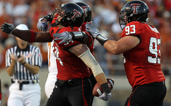 LUBBOCK, TX - SEPTEMBER 18:  Defensive end Scott Smith #94 of the Texas Tech Red Raiders celebrates a pass interception against the Texas Longhorns at Jones AT&T Stadium on September 18, 2010 in Lubbock, Texas.  (Photo by Ronald Martinez/Getty Images)