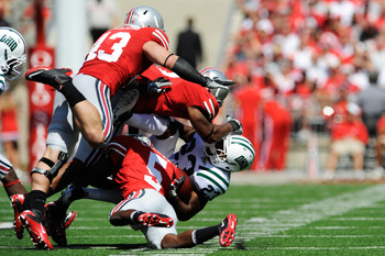 COLUMBUS, OH - SEPTEMBER 18:  Dallas Brown #23 of the Ohio Bobcats is gang tackled by Chimdi Chekwa #5, Jermale Hines #7 and Nathan Williams #43, all of the Ohio State Buckeyes at Ohio Stadium on September 18, 2010 in Columbus, Ohio.  (Photo by Jamie Saba