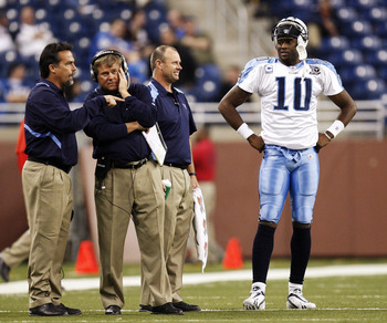 DETROIT , MI - NOVEMBER 27: Vince Young #10 of the Tennessee Titans talks with head coach Jeff Fisher, offensive coordinator Mike Heimerdinger and trainer Brad Brown after coming in the game in the fourth quarter against the Detroit Lions on November 27,