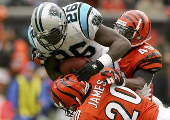 CINCINNATI - OCTOBER 22:  DeShaun Foster #26 of the Carolina Panthers is brought down by Tory James #20 and Madieu Williams #40 of the Cincinnati Bengals October 22, 2006 at Paul Brown Stadium in Cincinnati, Ohio.  (Photo by Matthew Stockman/Getty Images)