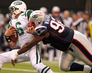 EAST RUTHERFORD, NJ - SEPTEMBER 19:  Mark Sanchez #6  of the New York Jets is sacked by Gerard Warren #92 of the New England Patriots on September 19, 2010 at the New Meadowlands Stadium  in East Rutherford, New Jersey.  (Photo by Al Bello/Getty Images)