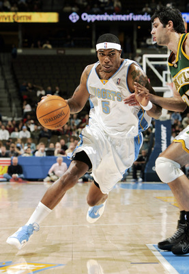 DENVER - NOVEMBER 9:  Rodney White #5 of the Denver Nuggets drives to the basket against Vladimir Radmanovic #77 of the Seattle SuperSonics in the first half at the Pepsi Center on November 9, 2004 in Denver, Colorado.  NOTE TO USER: User expressly acknow