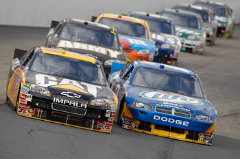 LOUDON, NH - SEPTEMBER 19:  Jeff Burton, driver of the #31 Caterpillar Chevrolet, and Kurt Busch, driver of the #2 Miller Lite Dodge, lead a pack of cars during the NASCAR Sprint Cup Series Sylvania 300 at New Hampshire Motor Speedway on September 19, 201