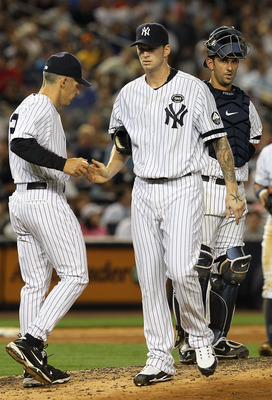 NEW YORK - AUGUST 02:  A.J. Burnett #34 of the New York Yankees hands the ball to manager Joe Giradi #28 as he leaves the game against the Toronto Blue Jays in the fifth inning on August 2, 2010 at Yankee Stadium in the Bronx borough of New York City.  (P