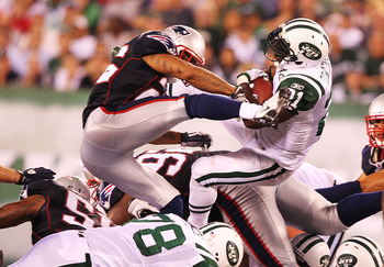 EAST RUTHERFORD, NJ - SEPTEMBER 19:  LaDainian Tomlinson #21  of the New York Jets leaps to a first down in the fourth quarter as Patrick Chung #25  of the New England Patriots delivers the hit during their  game on September 19, 2010 at the New Meadowlan