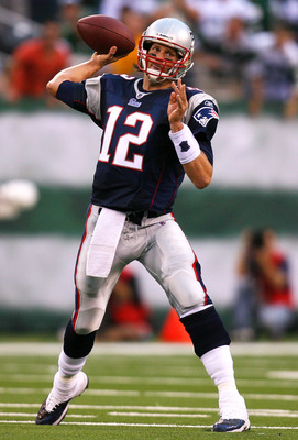 EAST RUTHERFORD, NJ - SEPTEMBER 19:  Tom Brady #12 of the New England Patriots drops passes against the New York Jets at the New Meadowlands Stadium on September 19, 2010 in East Rutherford, New Jersey. The Jets defeated the Patriots 28 - 14.  (Photo by A