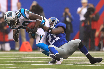 EAST RUTHERFORD, NJ - SEPTEMBER 12: Dwayne Jarrett #80 of the Carolina Panthers is tackled by Kenny Phillips #21 of the New York Giants during the NFL season opener at New Meadowlands Stadium on September 12, 2010 in East Rutherford, New Jersey.  (Photo b