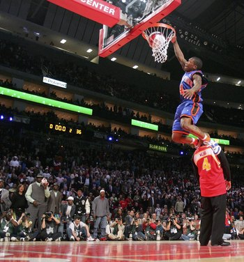 HOUSTON - FEBRUARY 18:  Nate Robinson #4 of the New York Knicks goes up for a dunk over former slam dunk champion Spud Webb in the Sprite Rising Stars Slam Dunk competition during NBA All-Star Weekend at the Toyota Center on February 18, 2006 in Houston,