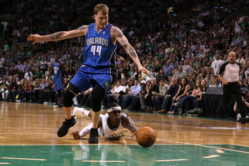 BOSTON - MAY 22:  Rajon Rondo #9 of the Boston Celtics dives for a loose ball against Jason Williams #44 of the Orlando Magic at TD Banknorth Garden in Game Three of the Eastern Conference Finals during the 2010 NBA Playoffs on May 22, 2010 in Boston, Mas