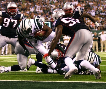 EAST RUTHERFORD, NJ - SEPTEMBER 19: Shonn Green #23 of the New York Jets is held short by the New England Patriots at the New Meadowlands Stadium on September 19, 2010 in East Rutherford, New Jersey. The Jets defeated the Patriots 28 - 14.  (Photo by Andr