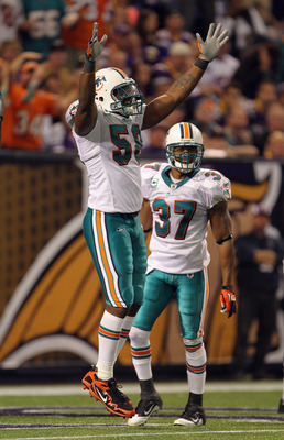 MINNEAPOLIS - SEPTEMBER 19:  Karlos Dansby #58 of the Miami Dolphins celebrates with Yeremiah Bell #37 after the Dolphins defense recovered a fumble in the end zone for a touchdown during the game on September 19, 2010 at Hubert H. Humphrey Metrodome in M