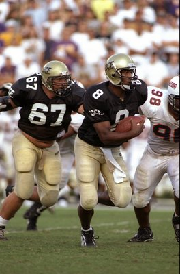 11 Oct 1997: Daunte Culpepper #8 of the Central Florida Golden Knights looks to run as teammate Ray Gould #67 guards him during the game against the Samford Bulldogs at Florida Citrus Bowl in Orlando, Florida. Central Florida defeated Samford 52-7. Mandat