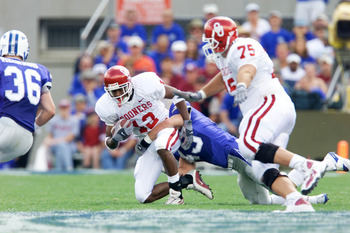 01 Sep 2001: Damian Mackey #13 of the Oklahoma Sooners is tackled by Andy Rule #49 of the Air Force Falcons during the game at Falcon Stadium in Colorado Springs, Colorado. Oklahoma won 44-3. DIGITAL IMAGE. Mandatory Credit: Brian Bahr/Allsport