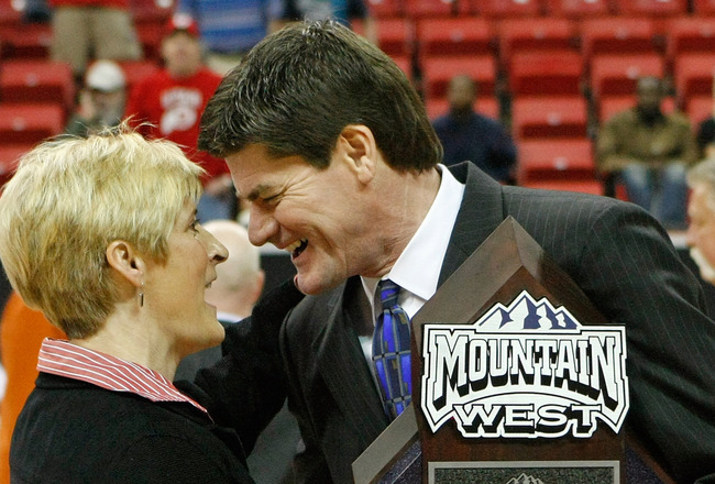 LAS VEGAS - MARCH 14:  Mountain West Conference commissioner Craig Thompson (R) presents the trophy to head coach Elaine Elliott of the Utah Utes after they defeated the San Diego State Aztecs 63-58 during the championship game of the Conoco Mountain West