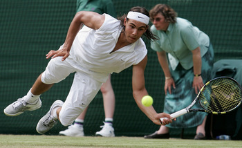 LONDON - JUNE 23:  Rafael Nadal of Spain dives for the ball against Gilles Muller of Luxembourg during the fourth day of the Wimbledon Lawn Tennis Championship on June 23, 2005 at the All England Lawn Tennis and Croquet Club in London.  (Photo by Phil Col